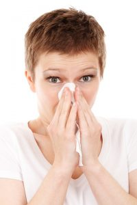 a woman with a tissue to her nose
